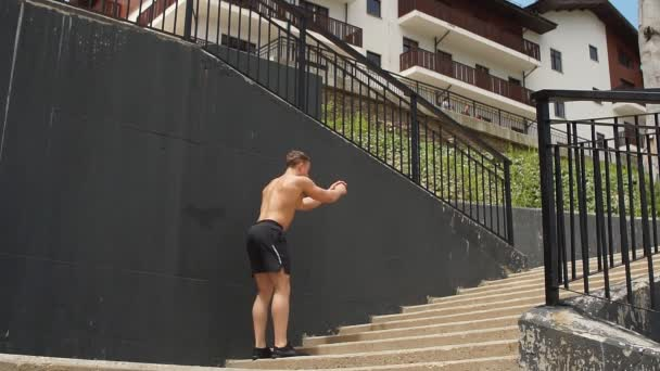 Young man athlete jumping upstairs on staircase and warming up before run