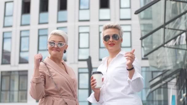 two adult Businesswoman boss posing back to back near office building
