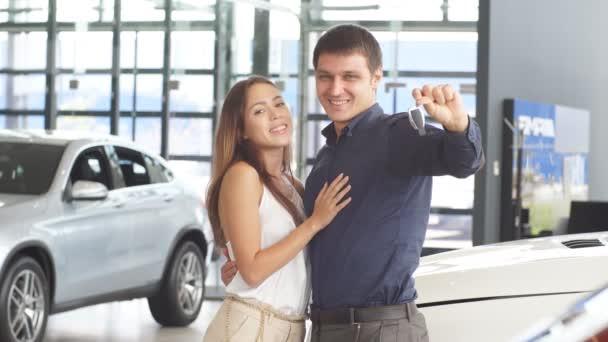 Šťastný milující pár objímající v blízkosti jejich nového luxusního auta v prodejně.