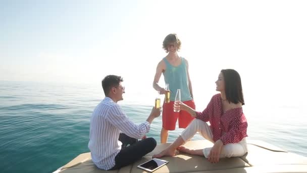 Friends making boat party having fun drinking beers and laughing together in sail sea