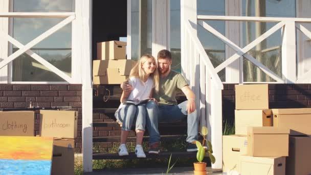 Mann und Frau stehen mit Kisten vor neuem Eigenheim