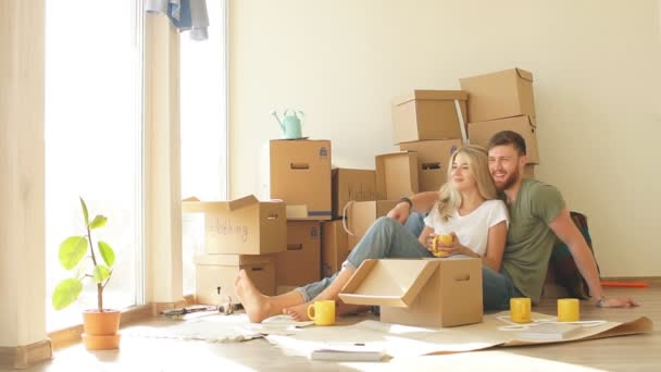 couple with book sitting on bed while moving into new home