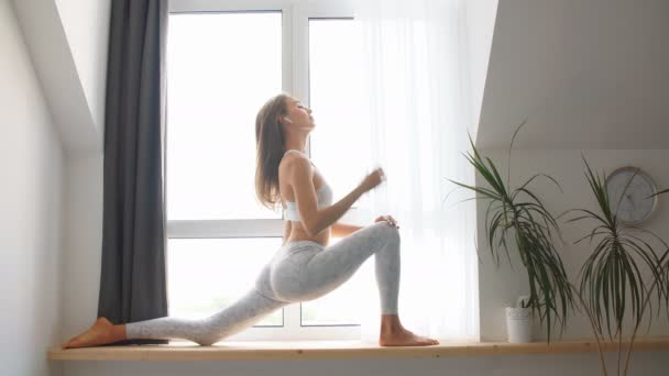 Woman practicing Warrior yoga pose indoors against window background