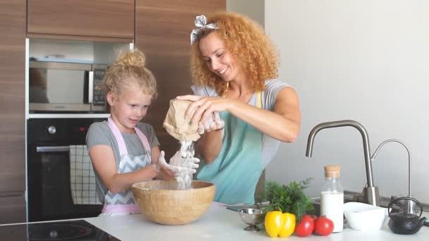 Dívka a její matka sypání mouky do misky a usmívat se při pečení