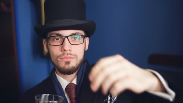 Handsome young man in a classic suit drinking whiskey in restaurant.