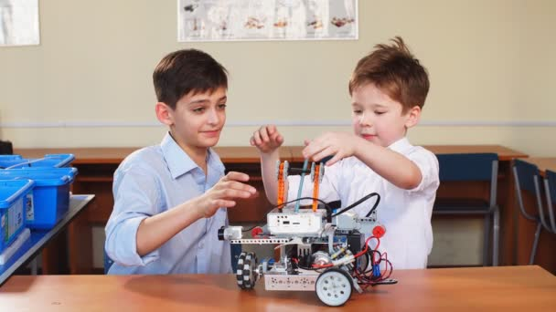 Kids playing with electrical robot while visiting robotics exhibition