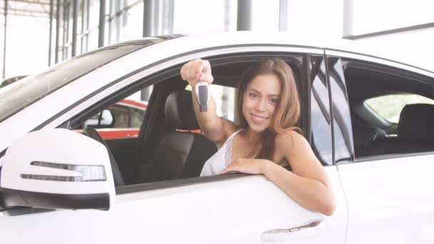 Happy woman driver in white car holds car keys in her new car at car show room