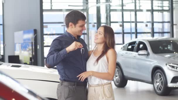 Boldog szerelmesek ölelkeznek az új luxusautójuk közelében a kereskedésben.