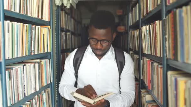 Fiatal Arab szakállas férfi diák választotta a könyv között a könyvtár polcain