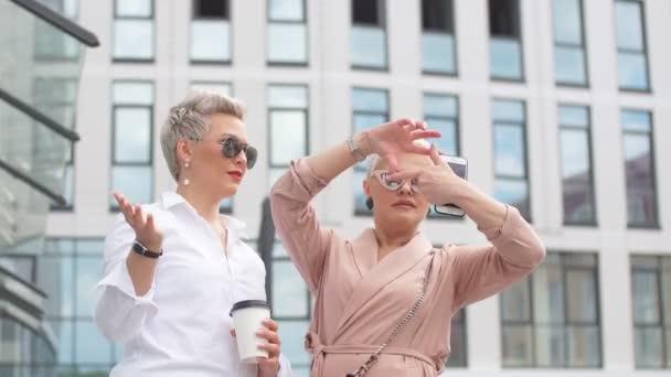 Dvě dámy obchodní v sluneční brýle představují vnější kancelářská budova