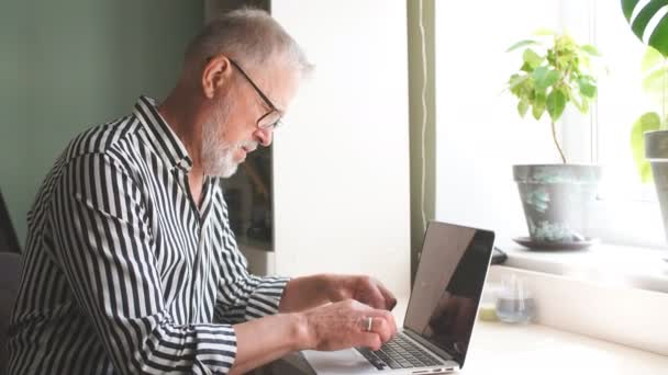 reifer bärtigen Mann von zu Hause aus mit Laptop. am Schreibtisch in der Nähe von Fenster