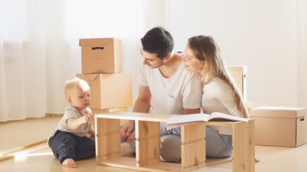Rodinné čtení instrukce a montáži nábytku spolu v obývacím pokoji nový byt hromadu přesouvání boxů na pozadí