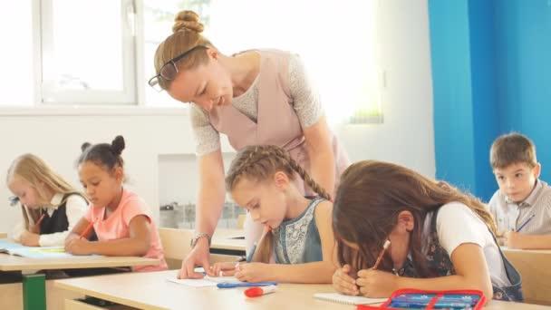 Učitel pomáhá dětem s domácím úkolem ve škole