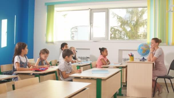 Skupina školních dětí všechny zvyšování jejich ruce ve vzduchu odpovědět