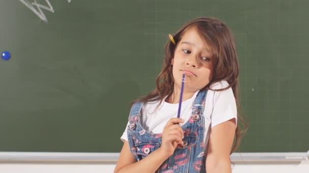 Átgondolt mosolygós kislány eszköztartási ceruzát portréja. Az ötlet zseniális gyermek