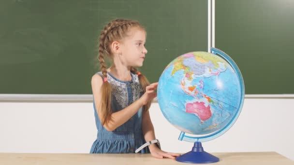 školy dívka s globe v učebně tabuli na pozadí