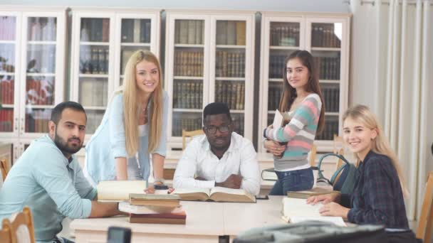 Group of multiracial people studying with books in college library.