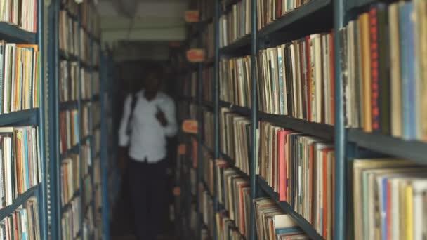 Blonďatá učitelka vyhledávání knih v knihovně, ve škole
