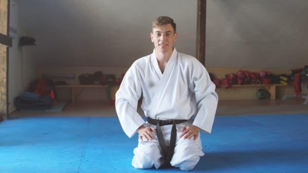 Fekete öves Karate ember ül a térd helyzetben, hogy Start vagy befejezni a harcot gyakorló