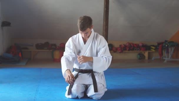 Karate kimonó ember ül térdre a harcművészetek edzőteremben emelet