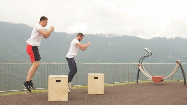 Dva mužské sportovní přátelé dělají box skok venkovní cvičení