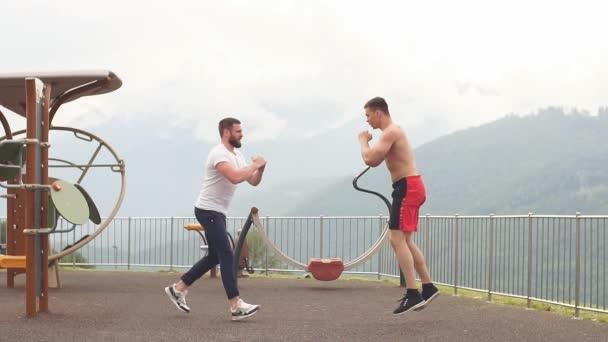 Boční pohled na dvě kavkazské sportovců dělat výpady v horách.