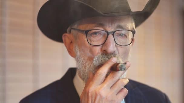 Elegantní starý muž v široké klobouk a bohaté modré Pánská oblek kouření doutníku vnitřní