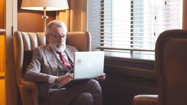 Modische älteren männlichen Schriftsteller tragen elegante Kleidung auf laptop.