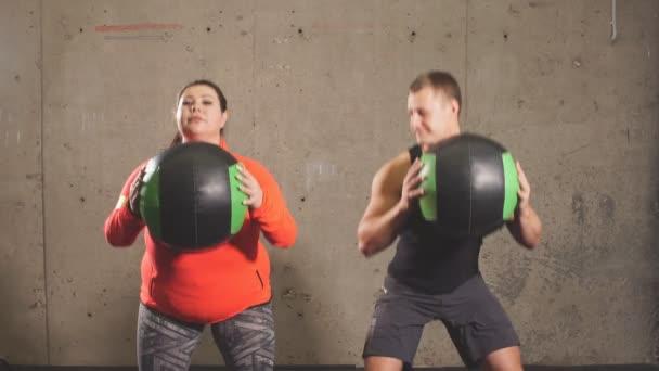 Emocionální pozitivní pár dělá cvičení s míčky ve fitness centru.