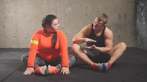 mladý aktivní příjemný osobní trenér mluvit se svým klientem při provozování sportu. fitness koncept