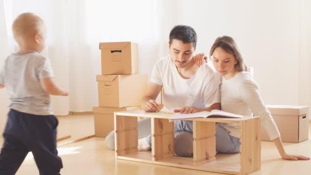 Familie zusammen im Wohnzimmer der neuen Wohnung beim Zusammenbau von Möbeln, Stapel von Umzugskartons im Hintergrund