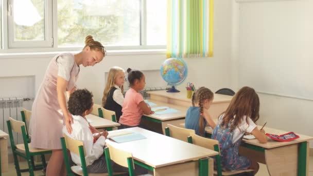 A tanár segít a gyerekeknek a házi feladatukban az iskolában.