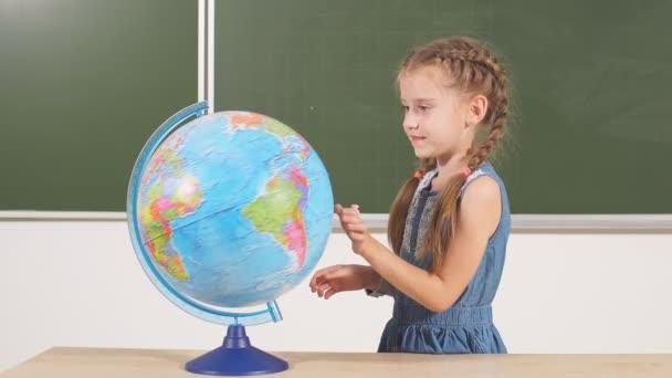 školní dívka s glóbus v učebně tabuli na pozadí