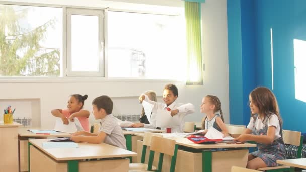 school kids have fun in class and throwing paper in air
