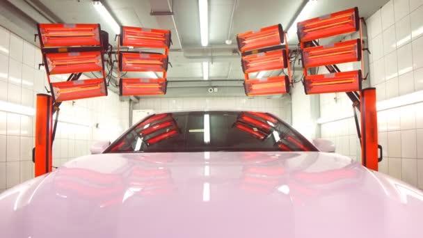 Červené lampy pro sušení keramického povlaku jsou za autem.