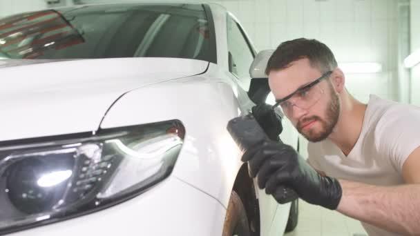 Mann überprüft Ergebnis der Politur des Autos mit Taschenlampe.
