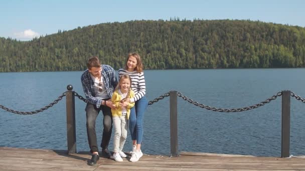 Portrait of happy family: Mother, father and child outdoors. Beautiful sporty family spends the fall holidays on nature.
