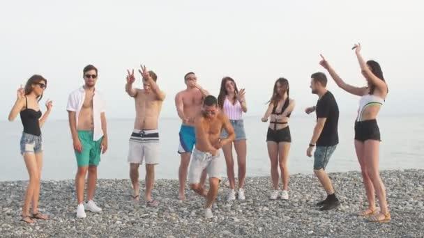 Friends dance on beach under sunset sunlight, having fun, happy, enjoy
