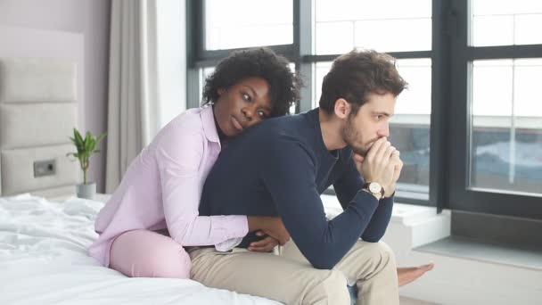 Attractive african girl comforting her upset boyfriend on sofa at home