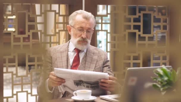 Alten Geschäftsmann mit Laptop im Kaffeepause in seinem Bürokonzept