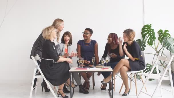 Positive women discuss organization plan while sitting at the table with laptop