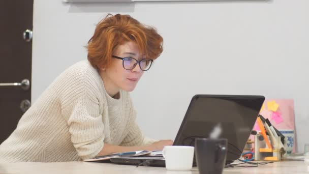 Concentrated businesswoman wearing glasses working late at night in office with computer.