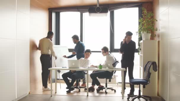 Smíšené rasy podnikatele v otevřeném prostoru kanceláře interiéru s panoramatickým oknem