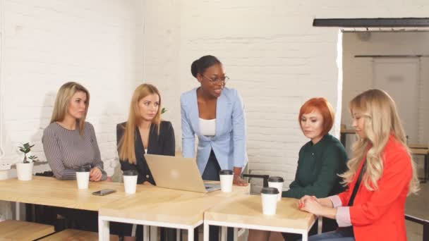 African female boss telling off her female employees, sitting in meeting room.