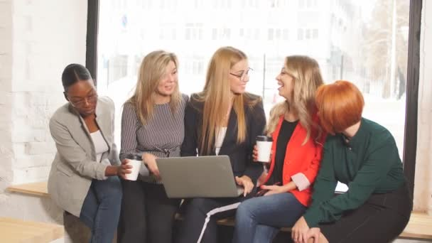 Group of multiracial businesswomen in casual wear looking at the laptop together