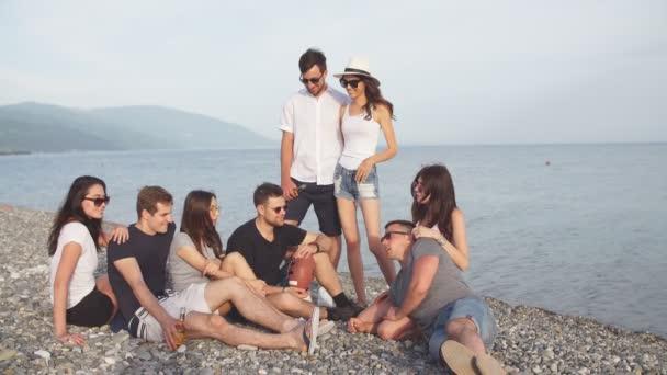 Baráti társaság bulizás és szórakozás a strandon naplementekor