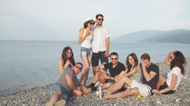 Vidám fiatalok, szép időt együtt, miközben ül a strandon