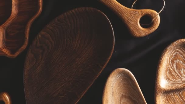 Rich variety of wooden empty cutting boards and plates on dark background. Mock up of dishes for restaurant serving