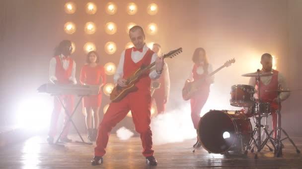 vtipný kytarista kontroluje nástroj před konsertem