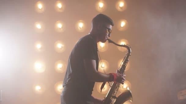 Mladý atraktivní hudebník hraje tenor saxofon na jevišti
